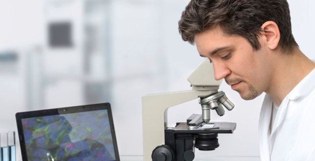 Researcher is working on microscope.